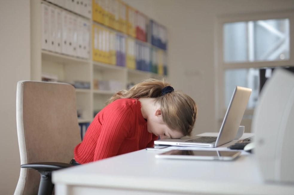 kvinde med hovedet på computeren